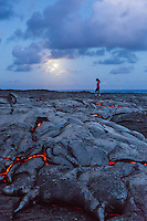 A woman walks by glowing lava under a full moon, Hawai'i Volcanoes National Park, Hawai'i Island.