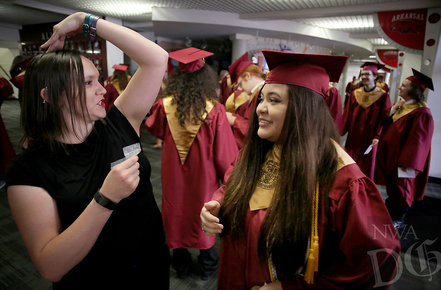 NWA Democrat-Gazette/DAVID GOTTSCHALK  Carmina Halbert, a graduating senior, is assisted Wednesday, May 17, 2017, by Mary Adams, sign language interpreter, with her cap at Barnhill Arena before graduation ceremonies of Rogers New Technology High School on the campus of the University of Arkansas in Fayetteville. The graduating class is the first to complete all four years at the school.