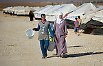 Two women walk through the Zaatari Refugee Camp, located near Mafraq, Jordan. Opened in July, 2012, the camp holds upwards of 50,000 refugees from the civil war inside Syria, but its numbers are growing. International Orthodox Christian Charities and other members of the ACT Alliance are active in the camp providing essential items and services.