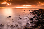 Ecuador, Galapagos Islands, San Cristobal Island. Ocean surf washing in on rocks with dramatic sky at sunset.