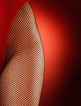 Sensual closeup of sexy woman hip in fishnet tights and red bodysuit  isolated on red background