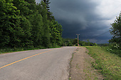 dark stormy clouds  over country road