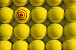 Rows of tennis balls with one ball with a bullseye drawn on it