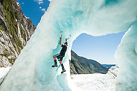 Ice climber enjoying spectacle of  beautifully coloured ice cave on Franz Josef Glacier,  Westland Tai Poutini National Park, West Coast, UNESCO World Heritage Area, South Westland, New Zealand, NZ