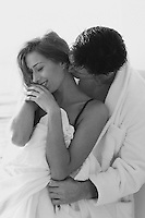 Man in a white robe kissing a woman's neck