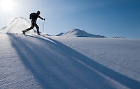 USA, Alaska, Curtis Smith snowshoeing on a sunny winter day in Turnagain Pass just off the Seward Highway. MR