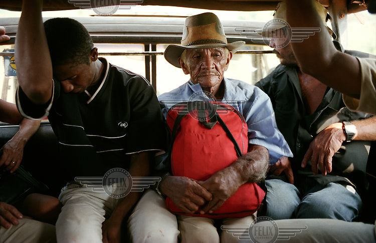 Workers are driven long distances to faraway farms in Para State. The trip is paid for by the 'gato' (cat - due to their propensity to land on their feet) who recruited them to work. This is the beginning of the workers' entrapment. It is a form of modern-day slavery, implicated most often via a fraudulent debt, such as the cost of the trip from their home to the farm, used as an excuse to keep workers in the farm while they owe money to the farmer. They are forced to buy everything, from tools to food, from the farmer's shop, at inflated prices. The debt is never cleared and the workers are effectively trapped.