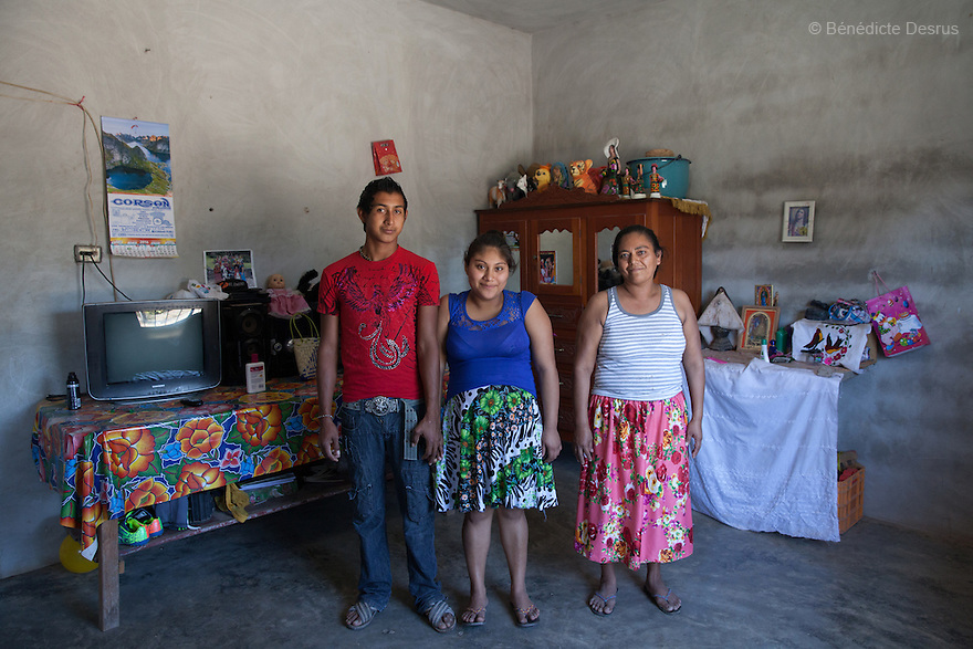 "Xhunaxhi Rosalía Santiago López (C) portrayed with her partner Rolando Luis López (L) and her mother Antonia López Guerra (R) at their home in Santa María Xadani, Oaxaca, Mexico on February 18, 2016. Xhunaxhi – her name means ""virgin"" in Zapotec – is 14 and lives with her 18-year-old partner and her mother, who had her own first child aged 17, in the town of Santa María Xadani in the southern Mexican state of Oaxaca. Xhunaxhi, who speaks little Spanish, is painfully shy and childlike and punctuates her comments with giggles. She is five months pregnant, but seems not to really understand – she has to ask her mother when her baby is due. She left school at 10 to travel with her family to Tepic, in the western state of Nayarit, for six-month stints working cutting sugar cane. She met her boyfriend last year, keeping the relationship secret from her mother, and was ""stolen"", according to the Zapotec tradition. She plans to marry legally at 18. While Mexico has outlawed marriage under the age of 18, many young girls become unofficial wives and mothers much earlier. In Juchitán, teenage pregnancy is expected, even prized. Mexico ranks first in teenage pregnancies among the member countries of the Organization for Economic Co-operation and Development (OECD). Photo by Bénédicte Desrus"