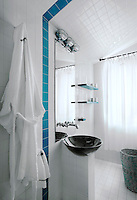 One blue strip of tiles runs from the ceiling down the wall in the otherwise all white tiled bathroom
