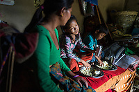 Kalpana Tamang (40), gets her younger daughter Binita (10) and son Sonam (7) ready for school as they have lunch in their temporary shelter in Kavre, Bagmati, Nepal on 30 June 2015.  Kalpana, a widow with 3 children, has been supported by SOS Children's Villages for many years now and had receive the Home-in-a-Box after the earthquake destroyed her house, almost killing her two daughters. She now lives in a temporary shelter, sharing her dwelling with farm animals, and is trying to make ends meet by weaving bamboo baskets to supplement the financial assistance provided by SOS Childrens Villages. The NGO mostly supports her children's welfare and schooling as well as provides her with essential household and schooling items like kitchen utensils and school books and uniforms. Photo by Suzanne Lee for SOS Children's Villages