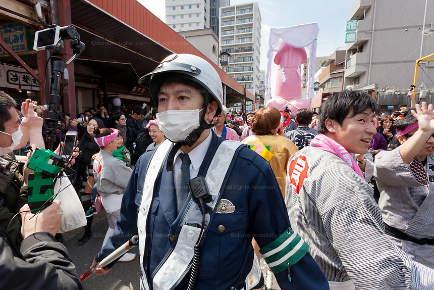 A policeman tries to control crowds at transvestites from the Elizabeth Club parade a large pink phallus on a mikoshi or portbale shrine during the  Kanamara matsuri or festival of the Steel phallus Kawasaki Daishi, Kawasaki, Kanagawa, Japan. Sunday, April 2nd 2017. The Kanamara Penis festival takes place on the first Sunday of April and celebrates the local legend of a penis eating demon who was defeated after being tricked into biting a steel phallus. The festival is popular with Japan's gay community and now uses its notoriety to raise money for HIV and AIDS charities. It is also wildly popular with foreign and Japanese.tourists.