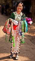 A smiling Hmong girl displaying festival costumes of the villagers.  The colorful outfits are worn at the time of the New Year festivities celebrated by the Hmong and other hill tribes in northern Laos. (Photo by Matt Considine - Images of Asia Collection)
