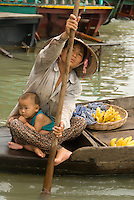 Mother selling her wares to tourists along the floating village near Siem Reap, Cambodia. The Vietnamese floating villagers on branches of Lake Tonie Sap, Cambodia are a unique nomadic community. With permission from the Cambodian government, they have built an entire floating community of houseboats, churches, clinics, shops and community centers on the river near Siem Reap, Cambodia. As the seasons change and the tides shift the entire village changes its location. The villagers rely on sales of fruits and soft drinks to the many tourists who have come by boat to see firsthand the hardships of life on a floating village. The Vietnamese are the most vulnerable of Cambodia's minorities, and the most prone to discrimination and violations of their rights.