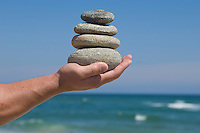 Hand balancing stack of stones with the ocean in the background