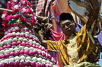 A villager with decorated eggs onboard his 'boat' at the Maulid Nabi festival, Cikoang, Sulawesi, Indonesia.