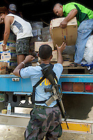 Philippines. Province Eastern Samar. Hernani. Town hall. 95 % of the town was destroyed by typhoon Haiyan's winds and storm surge. A policeman helps to unload food and non food items from a truck chartered by the Integrated Relief Drive for the Vicims of Typhoon Yolanda (ITAYO). The joined project is a mixed association, both public with PAGCOR (Philippines Amusement & Games Corporation) depending from the filipino government and private by Resort World Casino and Solaire Resort Casino Manila. The policeman is armed with an M-16 machine gun (a rifle adapted for semi-automatic and full-automatic fire) . Typhoon Haiyan, known as Typhoon Yolanda in the Philippines, was an exceptionally powerful tropical cyclone that devastated the Philippines. Haiyan is also the strongest storm recorded at landfall in terms of wind speed. Typhoon Haiyan's casualties and destructions occured during a powerful storm surge, an offshore rise of water associated with a low pressure weather system. Storm surges are caused primarily by high winds pushing on the ocean's surface. The wind causes the water to pile up higher than the ordinary sea level. 26.11.13 © 2013 Didier Ruef