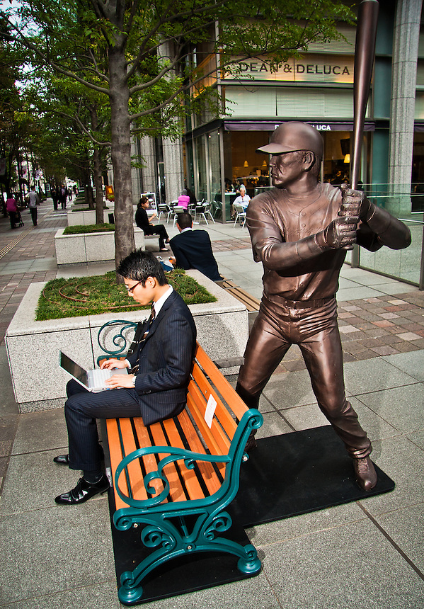 "Saleryman sitting on a bench about to be ""assulted"" by famous Baseball player Matsui ""Godzilla""."