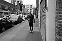 London, UK. 04.04.2015. Man, walking, listening to music, East London. Photograph © Jane Hobson.