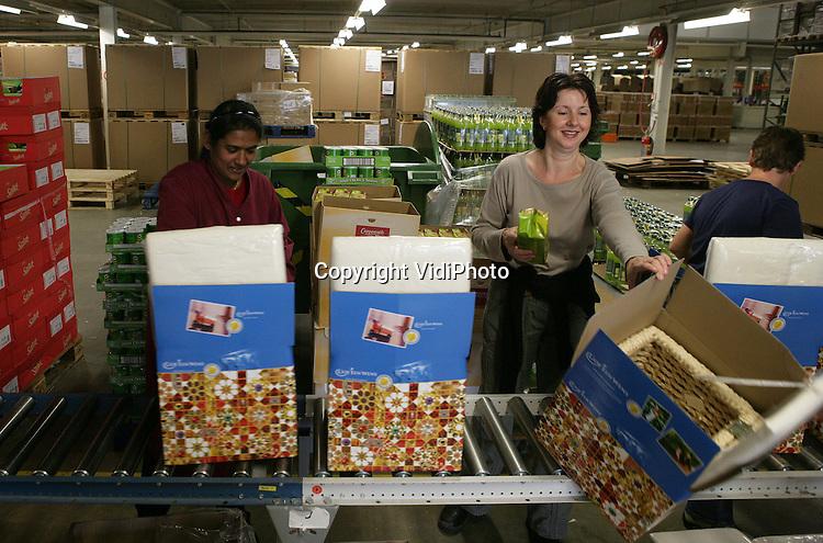 Foto: VidiPhoto..DUIVEN - Medewerkers van inpakcentrale ICN/Makro Feestpakketten in Duiven zijn begonnen met de productie van kerstpakketten. Dit jaar zijn dat er 1,2 miljoen, een stijging ten opzichte van vorig jaar. Reden is de aantrekkende economie en de voor het bedrijfsleven gunstige verruiming van de kerstpakkettenregeling. ICN is de grootste inpakcentrale van Nederland. De verwachting is dat er dit jaar in Nederland 4,9 miljoen kerstpakketten worden uitgereikt. Nieuwe trends zijn pokeren en de chocoladefontein.
