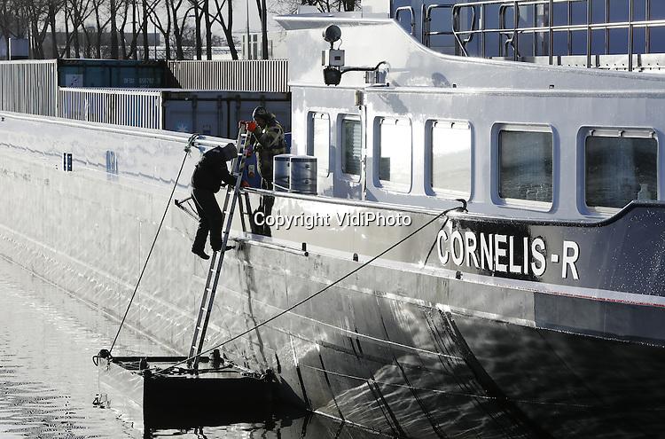 Foto: VidiPhoto<br /> <br /> WEURT - Binnenvaartschippers op het Maas-Waal kanaal bij Weurt (Nijmegen) maken woensdag van de nood een deugd met extra onderhoud van hun vrachtschepen. Zo'n 25 schippers zijn noodgedwongen werkloos omdat vanwege de stukgevaren stuw bij Grave, ook de sluis bij Weurt niet open mag. Daarmee zou het waterpeil tussen de Maas en de Waal nog verder zakken, met als gevolg grote schade aan de woonboten. Een ongeluk komt zelden alleen, want ook het waterpeil in de Waal is ongebruikelijk laag omdat er al weken geen regen van betekenis is gevallen. Op het Maas-Waal kanaal is het water 1.20 meter gezakt. De schippers voor de sluis bij Weurt liggen daardoor 'gevangen' tussen de Waal en de noodstuw bij Heumen. Binnenvaartschipper Mark Peters (53) van de 84 meter lange Dusky uit Angeren ligt al sinds vorige week donderdag stil met een lading kunstmest voor boeren in Zuid-Duitsland. Ook het transport van diervoeders van de Rotterdamse haven naar Duitsland loopt grote vertraging op. Zijn schade bedraagt rond de 1350 euro per dag.