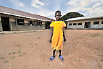 Neema Abba needed a new school, and UMCOR was there. The 7 year old stands in front of her new school in the Southern Sudanese village of Jombo. The school was constructed by the United Methodist Committee on Relief (UMCOR). Families here are rebuilding their lives after returning from refuge in Uganda. NOTE: In July 2011, Southern Sudan became the independent country of South Sudan