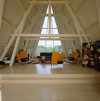The A-framed attic is furnished with contemporary seating and the rafters and ceiling struts accentuate the height of this dramatic space