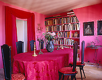 In this dining room-cum-library the walls are painted a bright candy pink, the antique table is covered in a fuschia brocade and the door is hung with a contrasting deep crimson curtain