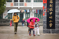 Woman and girls leave the playground of a primary school in Fuli. China has a one child policy to limit population.