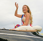 Wantagh, New York, USA. 4th July 2015. A finalist contestant in The Miss Wantagh Pageant ceremony, a long-time Independence Day tradition on Long Island, waves as she rides in backseat of a luxury convertible car, in the town's July 4th Parade. After the parade, the Miss Wantagh Pageant 2015 ceremony was held. Since 1956, the Miss Wantagh Pageant, which is not a beauty pageant, crowns a high school student based mainly on academic excellence and community service.