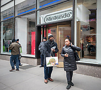 Shoppers leave Nintendo World with their Nintendo Switch consoles in Rockefeller Center in New York on the launch day of the new Nintendo Switch console on Friday, March 3, 2017. (© Richard B. Levine)