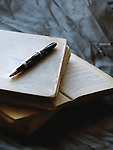 An old black pen laid on antique books, with a printed page in the centre, and a texturized grey/blue background.