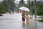 People walk through flooded streets in November 2014 in Meulaboh in Indonesia's Aceh province. Flooding in the region has grown worse because of climate change and the proliferation of palm oil plantations.