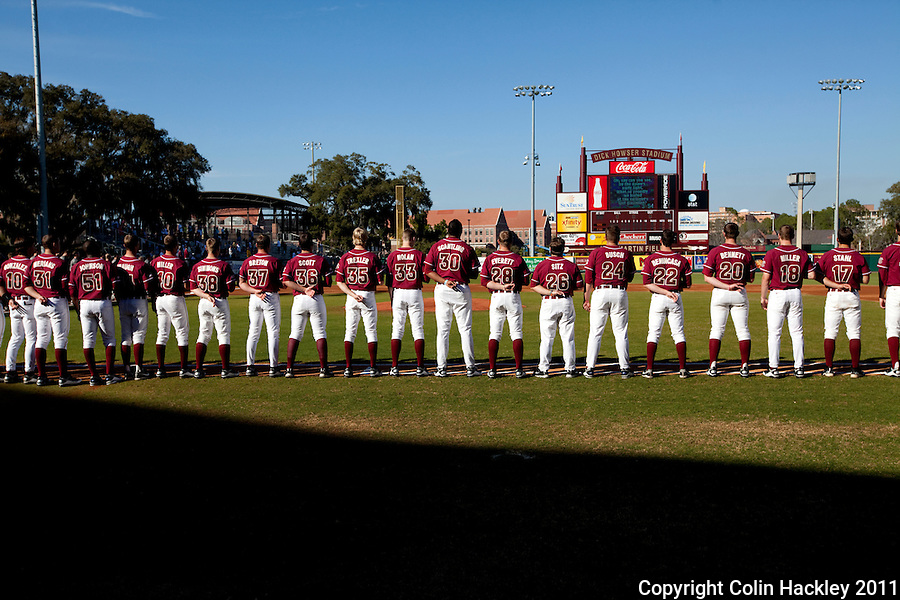 TALLAHASSEE, FL 2/18/11-FSU-VMI BASE11 CH-Florida State players stand for the National Anthem at the start of the Virginia Military Institute game Friday at Dick Howser Stadium in Tallahassee. The Seminoles beat the Keydets 12-0 in the season opener for both teams..COLIN HACKLEY PHOTO