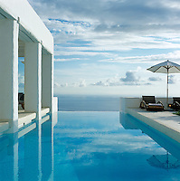 Parasols and a covered roof terrace beside an infinity pool