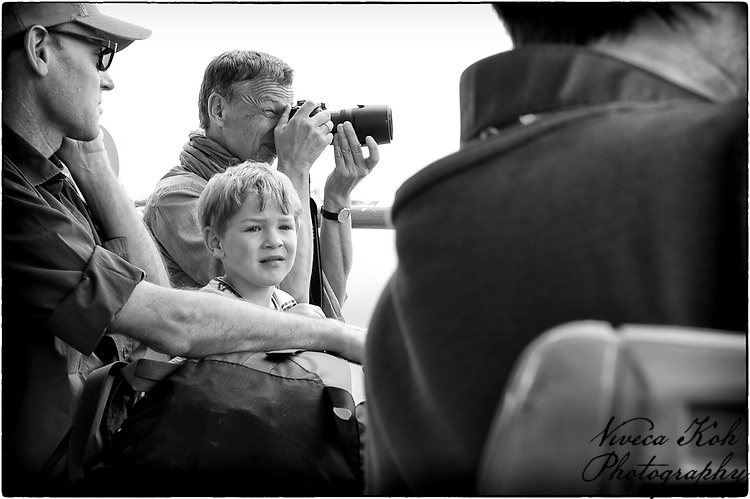 People on Vaporetto boat in Venice, including child and photographers.
