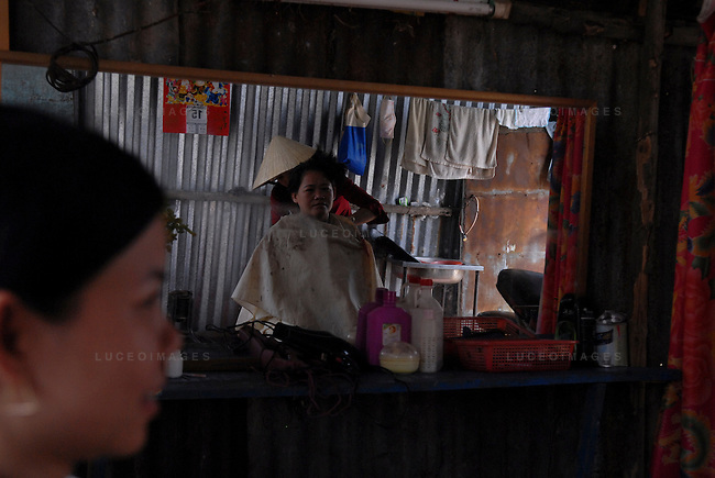 A woman gets her haircut at a barber shop in Can Tho, Vietnam.