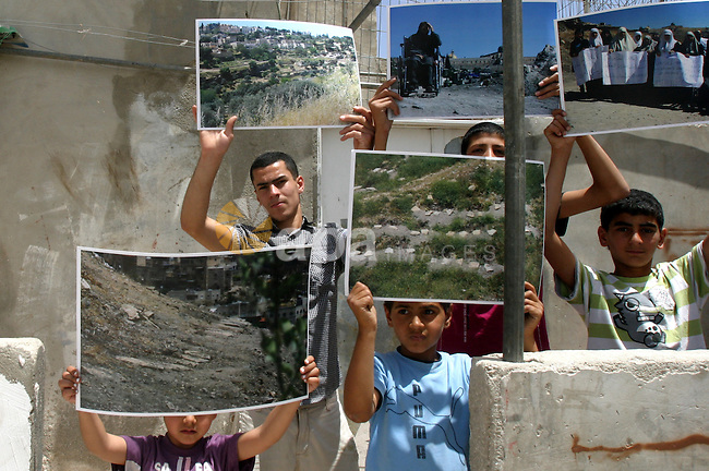 Palestinian children hold pictures of the judaized land during a press conference discusses the issue of judaizing Jerusalem and  the alleged Jewish graves in Valley Rababa, in Silwan Jerusalem's old city, In Jerusalem on May 28, 2012. Photo by Mahfouz Abu Turk