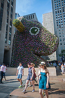 "Visitors observe Jeff Koons' sculpture ""Split-Rocker"" unveiled in Rockefeller Plaza in New York on Wednesday, June 25, 2014. The 37-foot high topiary sculpture consisting of over 50,000 flowering plants will be on display until September 12. The exhibit coincides with a retrospective of Koon's work at the Whitney Museum of American Art. (© Richard B. Levine)"