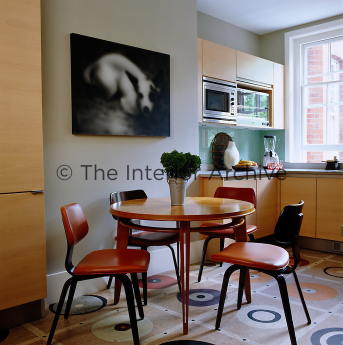 The kitchen has a colourful patterned linoleum floor and 1950s style table and chairs that give it a retro feel