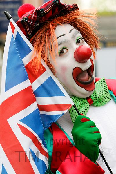 Clown street entertainer with patriotic Union Jack flag, Windsor, Berkshire, UK