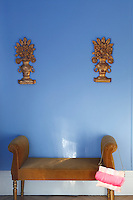 In the dining room two sculptured antique reliefs hang above a banquette upholstered in gold velvet