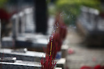 A stick of incense burns on a grave at Truong Son Martyrs Cemetery in Quang Tri province, Vietnam. The cemetery contains the graves of about 10,300 communist soldiers who died along the Ho Chi Minh Trail supply network into South Vietnam during the conflict from 1959 to 1975. April 24, 2013.
