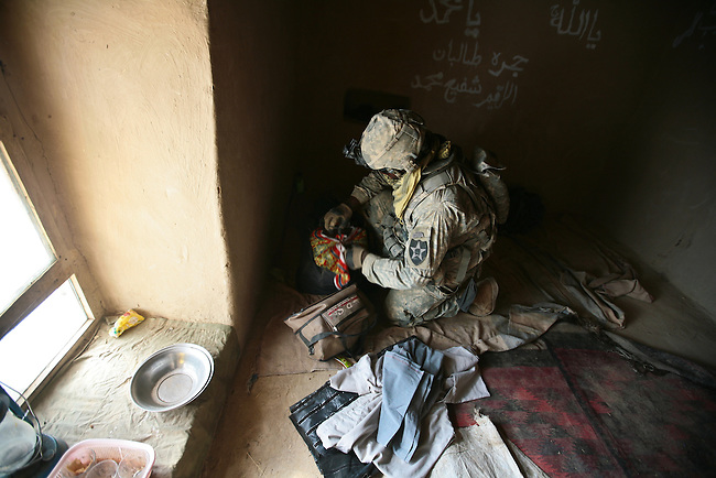 Sgt. Noah Robert, 30, of Long Island, N.Y., a soldier with Company C, 4th Battalion, 23rd Infantry Regiment, searches through bags of clothing and other items inside a madrassa, or religious school, that villagers had identified as belonging to the Taliban. According to an interpreter for U.S. forces, graffiti inside the building appeared to have been written by Taliban fighters. Oct. 26, 2010. DREW BROWN/STARS AND STRIPES