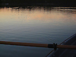 An early morning row on Nelson Bay in the San Juan Islands with flat calm water and pastel colors of the imminent sunrise reflected; one oar raised
