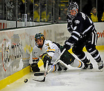 1 February 2008: University of Vermont Catamounts' forward Wahsontiio Stacey, a Freshman from Kahnawake, Quebec, lunges for the puck against University of New Hampshire Wildcats' defenseman Craig Switzer, a Senior from Peachland, BC, at Gutterson Fieldhouse in Burlington, Vermont. The seventh-ranked Wildcats defeated the Catamounts 5-1in front of a sellout crowd of 4,003...Mandatory Photo Credit: Ed Wolfstein Photo
