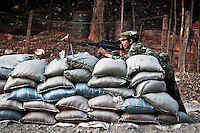 A KIA soldier stands guard at his post just 100 meters away from the Burmese army position at one of the frontines some kilometers from the Kachin rebel stronhold Laiza city, the headquarters of the Kachin independence Army. Fierce clashes have taken place since the ceasefire was broke by the Burmese army last June 2011. During months the fighting were spread out along the Kachin State leaving more than 40,000 displaced persons and refugees (a conservative estimating) in accord with the humanitarian aid groups.