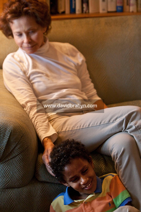 Marilyn Berger (background), widow of Don Hewitt, touches Danny Hodes, the 8 year-old Ethiopian boy she has taken in, as he sits at her feet in her apartment in New York, NY, USA, 9 April 2010. Ms Berger met him in Addis Ababa while reporting there and helped him get surgery.