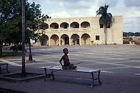 Proud looking Dominican boy sitting on a bench in front of the Alcazar de Colon in old Santo Domingo,  Dominican Republic. This Spanish Colonial palace was built in the early 16th century for Christopher Colubus' son, Diego Columbus. It is now open to the public.