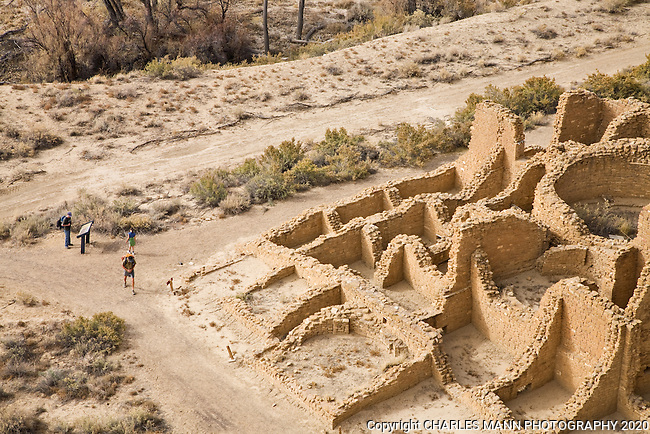 Chaco Canyon hikers at the Alto Mesa trailhead walk past the Kin Kletso Pueblo ruins on their way up to the top of the mesa at Chaco Culture National Historica Park.