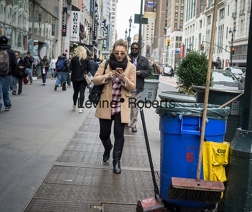A shopper texts while walking in Midtown Manhattan in New York on Friday, March 18, 2016. (© Richard B. Levine)